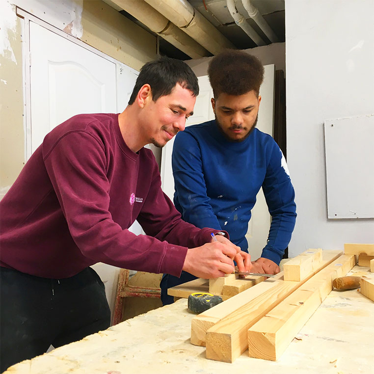 Tutor demonstrating accurate measurement in woodwork to a school student