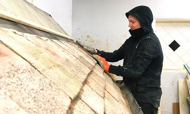 Student learning to place roof tiles