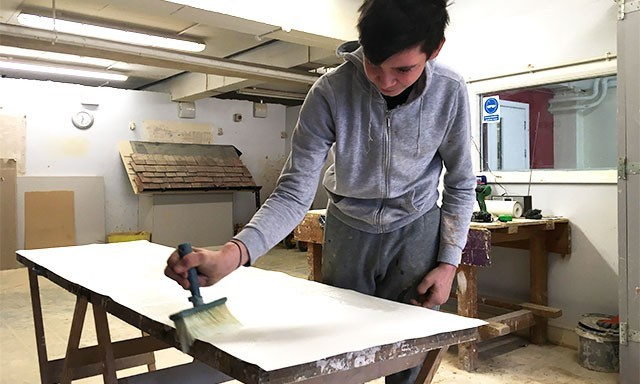 School student learning to paste and apply wallpaper